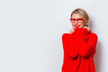 Portrait of a beautiful white smiling woman in red sweater on white background, isolated.