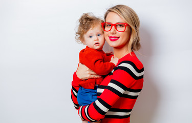 Portrait of a beautiful white smiling woman in red sweater with child on white background, isolated.