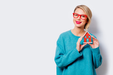 Portrait of a beautiful white smiling woman in blue sweater with dream house on white background, isolated.