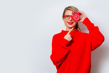 Portrait of a beautiful white smiling woman in red sweater with little alarm clock on white background, isolated.