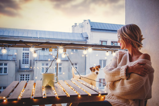Young woman with cup of coffee sitting at table in near fairy lights in evening time.