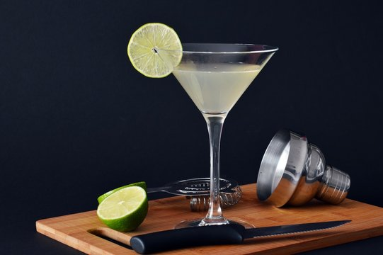glass of daiquiri cocktail on wooden chopping board and black background
