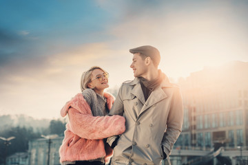 Come with me. Toned portrait of young loving couple enjoying romantic date with beautiful sky on background. Gentleman in flat cap looking at girlfriend with love and keeping hands in pockets