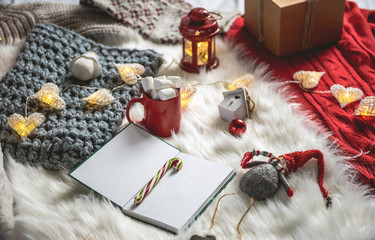 Red mug of delicious guimauve and notebook with candy locating on rug. Christmas decor concept