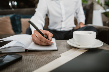 Close up of male hand handling pen and writing down notes in sketchbook. He is having mug with hot drink and using phone while doing some business in informal atmosphere