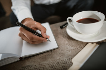 Top view close up of male hand holding pen and making notes in his business diary. He is drinking hot beverage in large mug