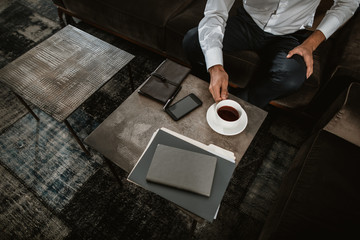 Top view of coffee table with mobile phone and stationary. Man is sitting on couch beside and drinking tea