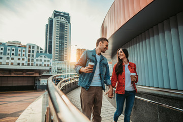 Smiling man telling with cheerful girl while tasting mugs of delicious liquid during relax outdoor. They holding hands together Fototapete