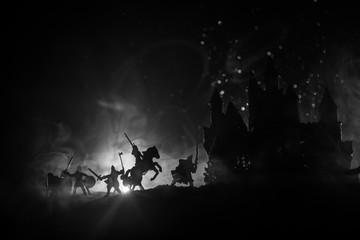 Medieval battle scene with cavalry and infantry. Silhouettes of figures as separate objects, fight between warriors on dark toned foggy background with medieval castle. Night scene. Selective focus