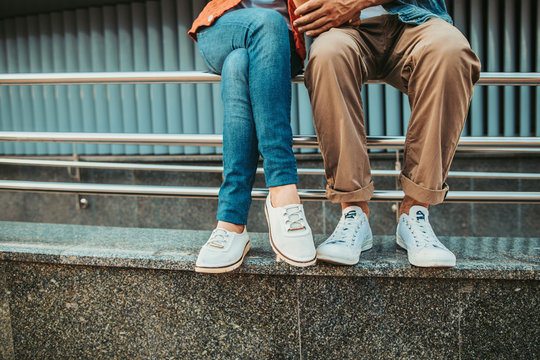 Close up female and man legs wearing modern white shoes. They having leisure on handrail outdoor