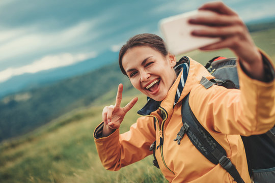 Cheerful nice woman smiling and making selfies while resting on the mountain hills