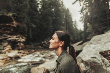 Positive nice young woman smiling while standing in the forest and breathing fresh air