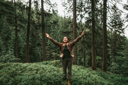 I am happy and free. Full length portrait of spirited young lady with closed eyes enjoying travel in the woods. She is spreading arms with joy and smiling