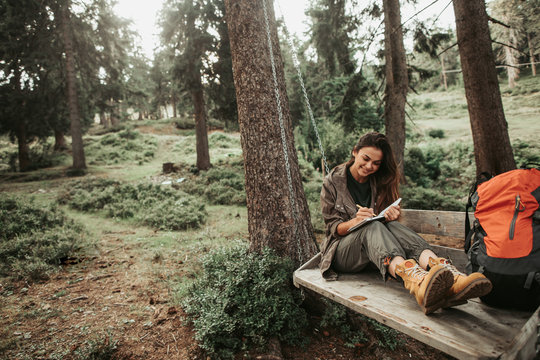 This is important. Portrait of beautiful young lady writing in notebook and smiling. Trees and green plants on background