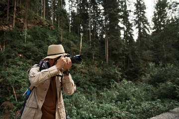 Professional photographer. Careful attentive experienced photographer traveling in deep forest and taking beautiful pictures