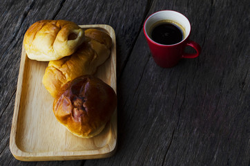 Espresso coffee red cup and Tasty buns on wood table backgrounds