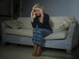 depressed and anxious beautiful blonde woman suffering depression and anxiety crisis feeling frustrated and thinking lonely at home sofa couch looking helpless in pain