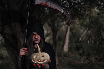 Woman ghost horror her have scythe and pumpkin on hand in forest,