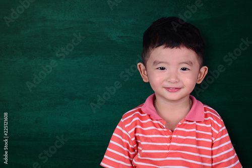 44c090246 Happy Asian kid smiling on empty green chalkboard with copy space ...
