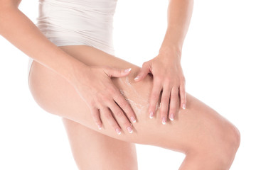 Female hands massage leg of woman with body lotion, close up