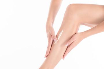Female hands applying cream on the skin of her leg, close up