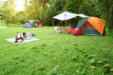 nature landscape camping tent with tarp and child family under tree on green grass meadow in jungle garden or forest for vacation picnic on holiday relax travel and summer or rainy with sunlight