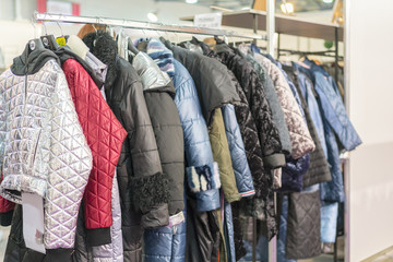 Winter Jacket in Winter Sale on a clothes rack. Women's coats on hangers in a women's clothing store