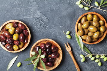 Natural olives in bowls with olive branch on black stone table top view.