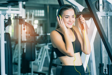 Woman Listening Music, Doing Workout Exercises.Relaxing After Fitness Training in gym.She smile and happy.