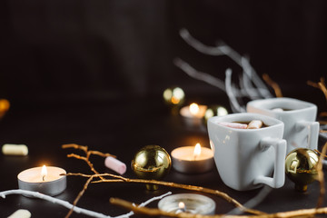 Christmas composition. Two cups of coffee with marshmallows, branches, candles and Christmas toys on a dark background.