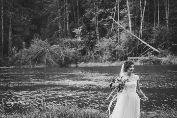Young bride in an elegant dress is standing near lake and holding bouquet of flowers and greens with ribbon on nature in the park. Black and white photo.