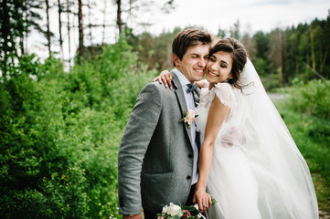 Attractive couple newlyweds on track in the garden. Outdoors. Romantic wedding moment.