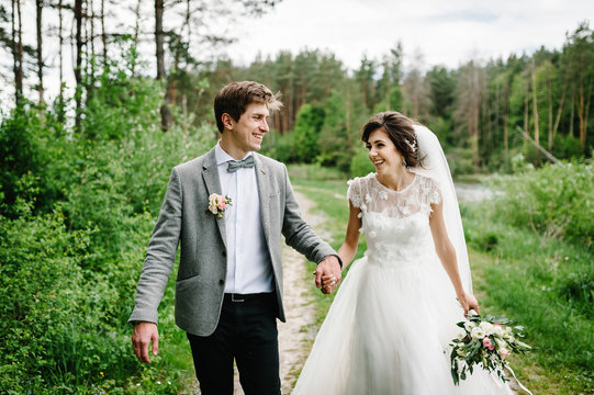 Romantic couple newlyweds, bride and groom is walking on a trail in an green park. Happy and joyful wedding moment.