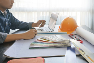 architect working on table with laptop and construction tools - business and industrial concept