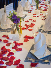 Table served with glasses and rose petals in the restaurant.