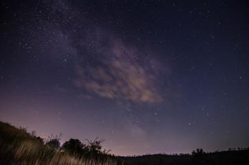 sternenhimmel mit wolken und wiese