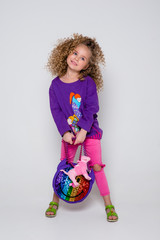 Bright curly girl in a studio, fashion kid, young model