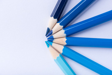 Macro photograph of several pencils of blue color on a white background