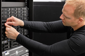 Male Technical Consultant Adjusting Hard Drives In SAN At Datace