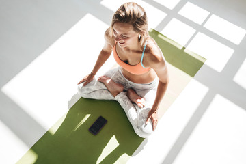Top view of adult fit woman practice yoga lotus pose on fitness mat, using smartphone early sunny morning in white gym