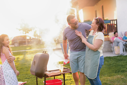 Picture of middle age couple making barbeque in their backyard. Family lunch on summer day.