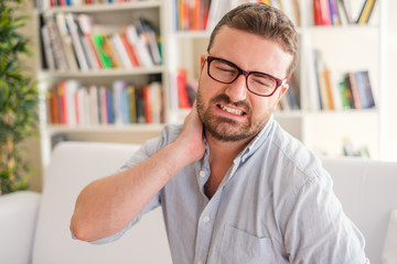 Man feeling pain to the neck at home