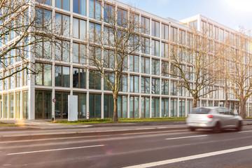 Hochhaus mit Glasfassade an der Straße mit fahrendem Auto