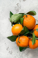 Fresh mandarins with leaves on a concrete table. Top view. Vertical photo.