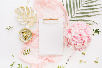 Modern home office desk workspace with blank paper clipboard, pink hydrangea flowers bouquet, tropical palm leaf, pastel blanket, monstera leaf plate and accessories on white background. Flatlay.