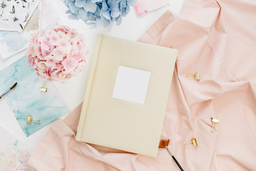 Artist home office desk with family wedding photo album, pastel colorful hydrangea flower bouquet, peachy blanket, decoration on white background. Flat lay, top view.