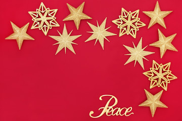 Christmas abstract background with gold glitter bauble decorations and peace sign on red with copy space.  Traditional festive card for the Christmas holiday season.