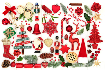 Symbols of Christmas with retro and new bauble decorations, winter flora, food, gift boxes, food, ribbons and bows on rustic white wood background. Top view.