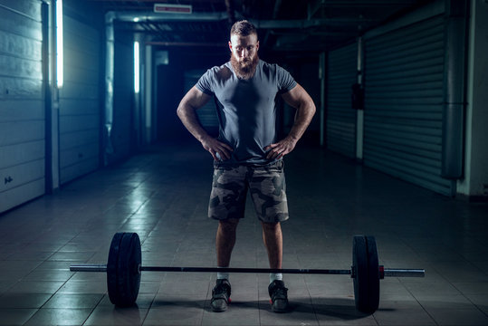 Picture of strong sporty bodybuilder preparing him self for heavy lifting. Standing in front of heavy weight in dark room.