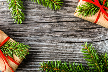 Holiday frame banner with christmas gift boxes, presents and fir tree branches, flat lay on wooden rustic background, mockup